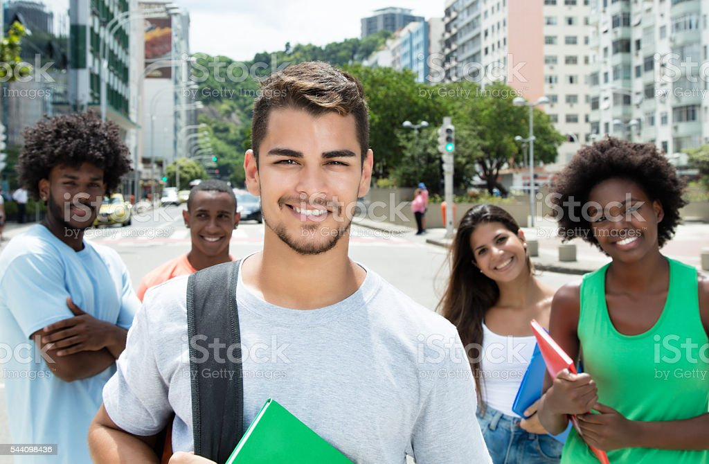 Hispanic male student with international friends stock photo