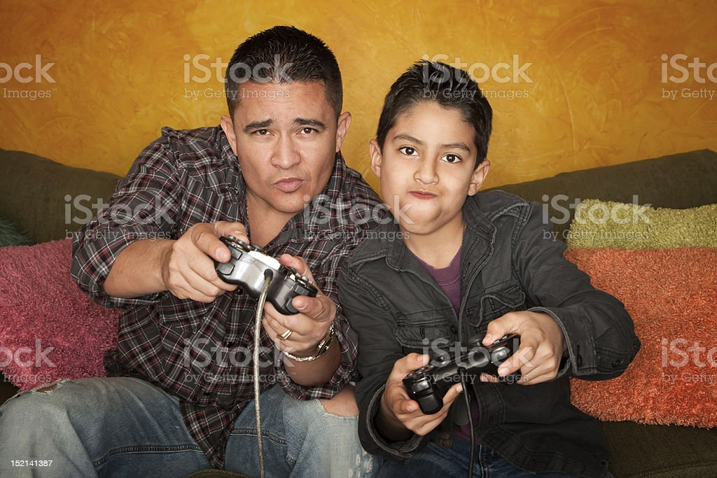 Hispanic Man and Boy Playing Video game royalty-free stock photo