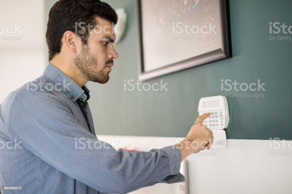 Hispanic man arming his alarm system stock photo