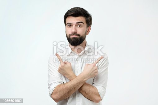 istock Hispanic man choosing between two options concept. He points to different sides by his fingers. 1086604662