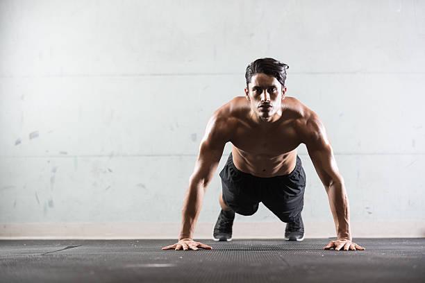 hispanic man doing push ups - push up stock photos and pictures