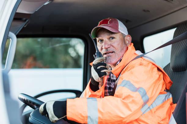 hispanic man driving a truck - talk in a radio foto e immagini stock