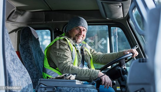 A mid adult Hispanic man in his 30s driving a truck. He is smiling at the camera.
