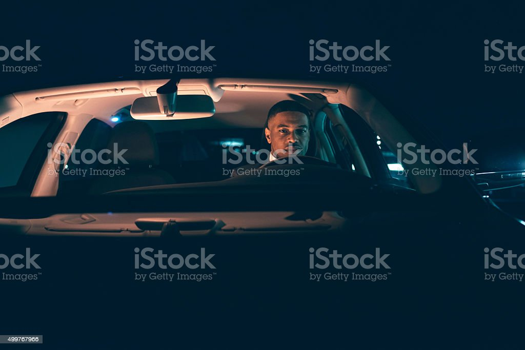 Hispanic man driving car at night. Front window view. stock photo