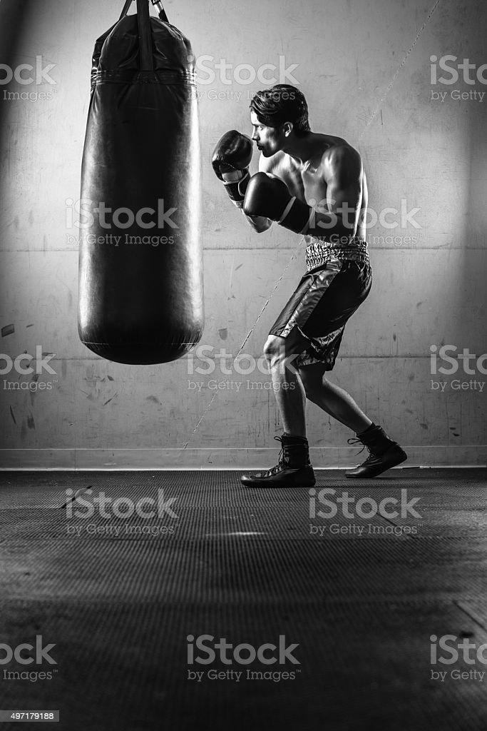Homme hispanique frapper le sac de boxe noir et blanc - Photo