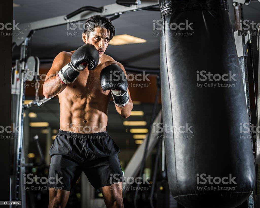 Hispanic Man Hitting A Punching Bag stock photo