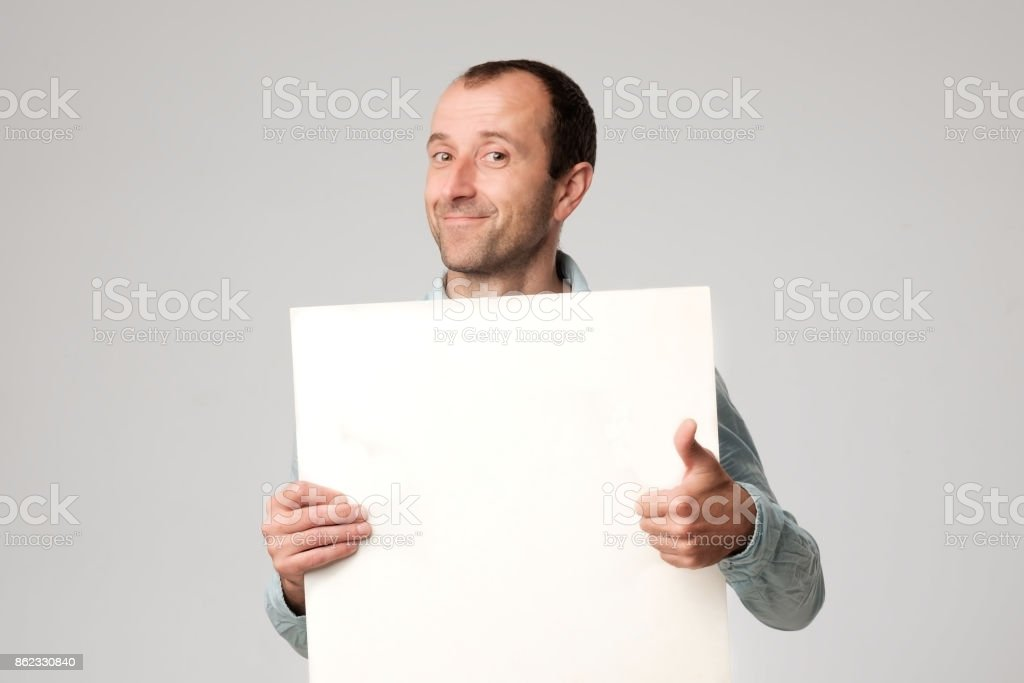Hispanic man holds the blank sign in a studio white background. stock photo