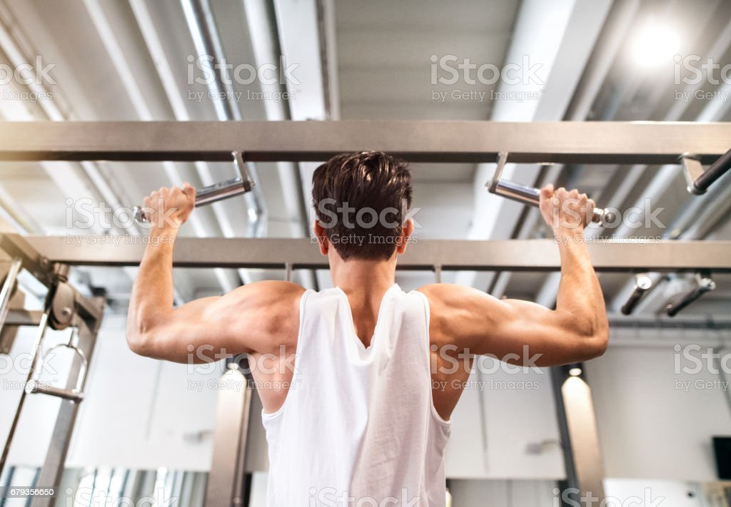 Hispanic man in gym doing pull-ups on horizontal bar. royalty-free stock photo