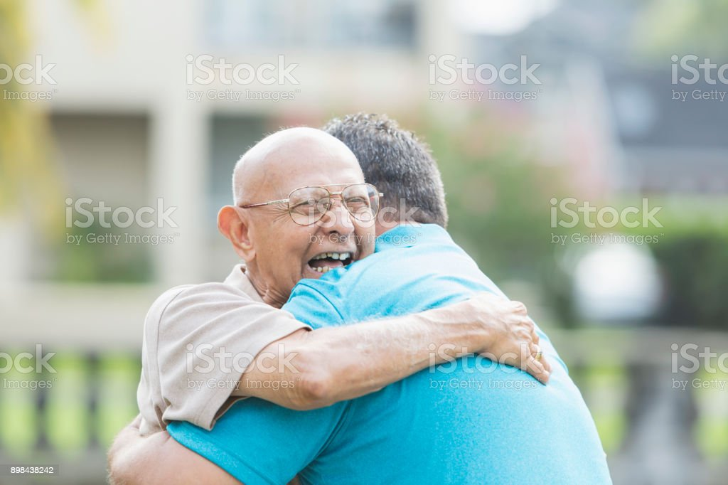 Hispanic man in his 90s, hugging adult grandson stock photo