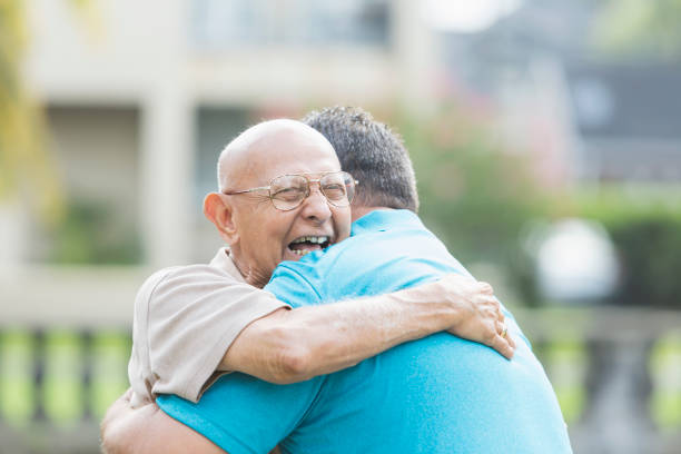 hispanic man in his 90s, hugging adult grandson - reunion stock photos and pictures