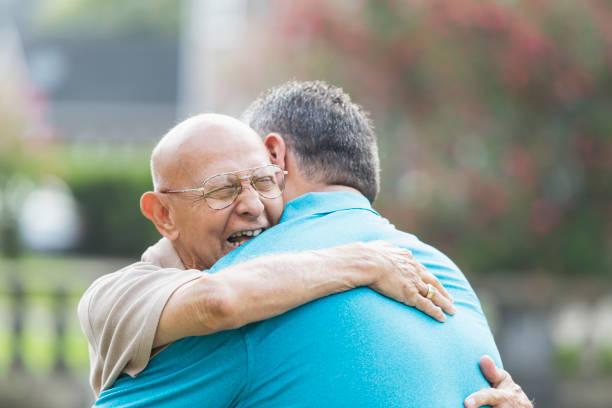 hombre hispano en su 90s, abrace a nieto adulto - reunión familiar fotografías e imágenes de stock
