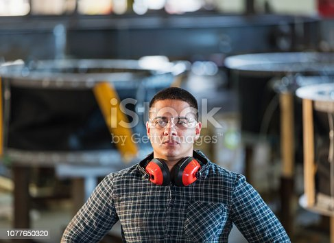 A mid adult Hispanic man in his 30s working in a manufacturing facility specializing in metal fabrication. He is standing with his hands on his hips, looking at the camera with a serious expression.