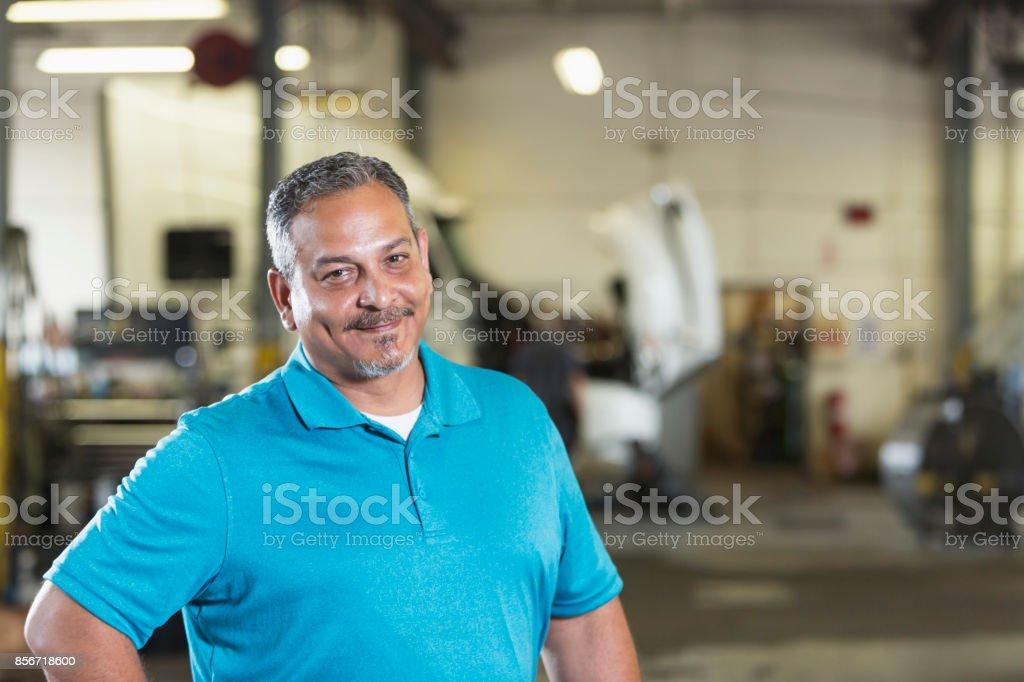 Hispanic man in vehicle repair shop stock photo