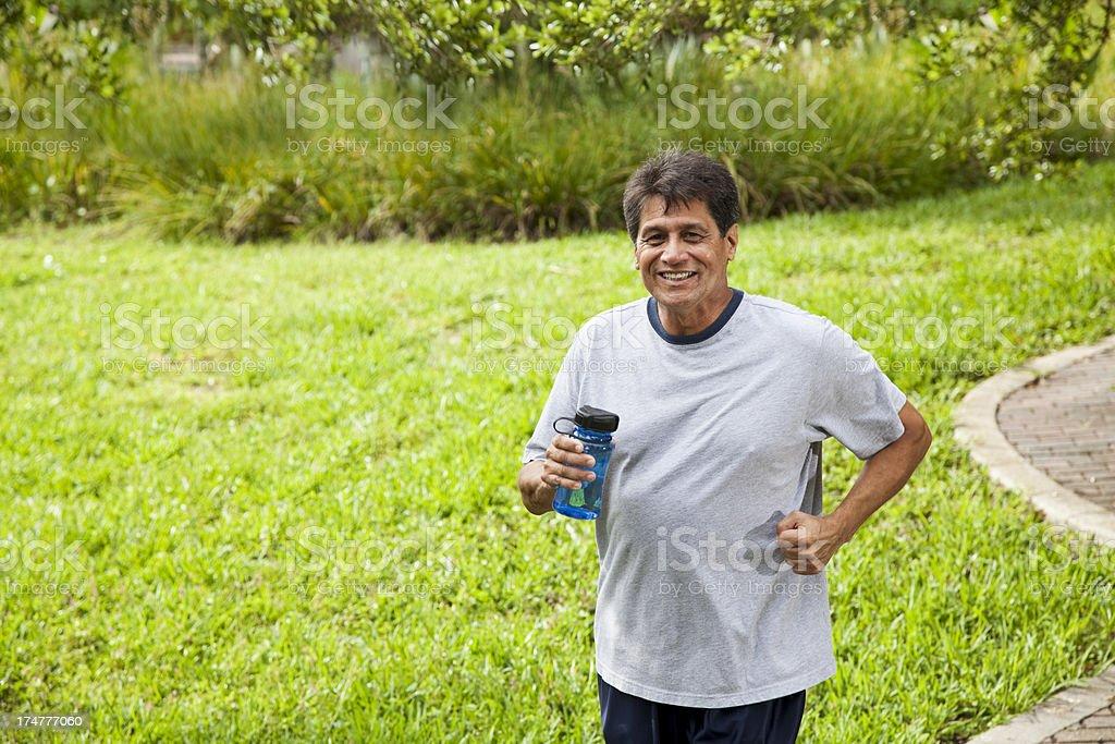 Hispanic man jogging stock photo