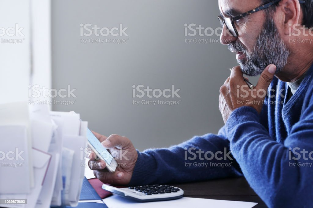 Hispanic Man Looks At His Mobile Phone As He Pays His Bills stock photo