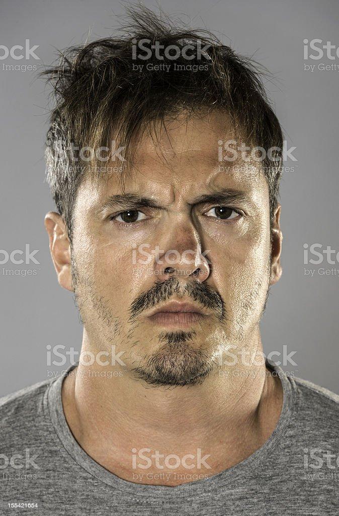 Serious and messy Hispanic man mug shot on gray background