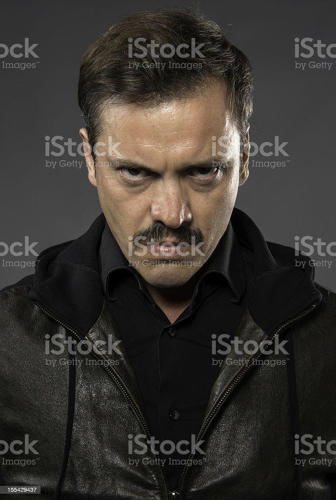 Serious and Hispanic man mug shot on gray background