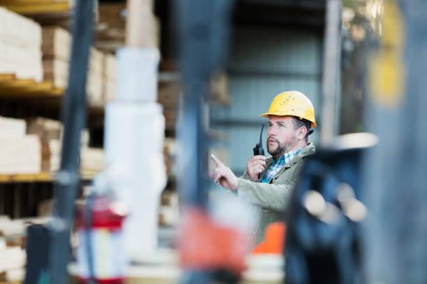 Hispanic Mann auf Walkie Talkie, arbeiten in Holzhof – Foto