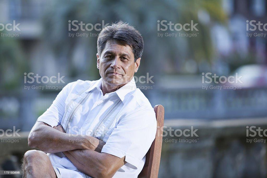 Hispanic man relaxing in park stock photo