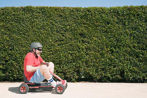 Hispanic man riding child's toy