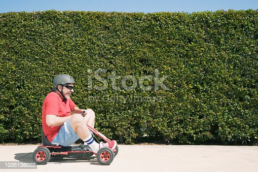 istock Hispanic man riding child's toy 1035136022