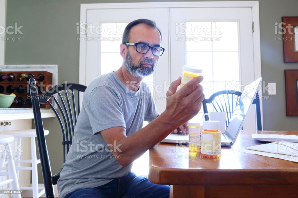 Hispanic Man Sitting At Dining Room Table Looking At His Prescription Medications stock photo