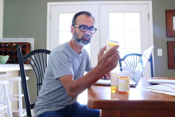 Hispanic Man Sitting At Dining Room Table Looking At His Prescription Medications stock photo
