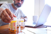 A Hispanic man in his late fifties reaches for one of his prescription medication bottles as he sits at his dining room table.  His laptop computer is open in front of him while sunlight filters in through the window behind him bathing the room with a soft glow of light.