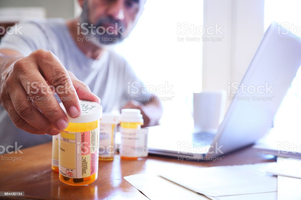 Hispanic Man Sitting At Dining Room Table Reaches For His Prescription Medications stock photo