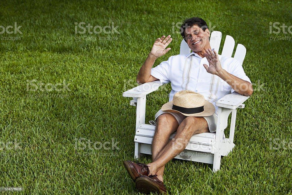 Hispanic man sitting in adirondack chair laughing stock photo