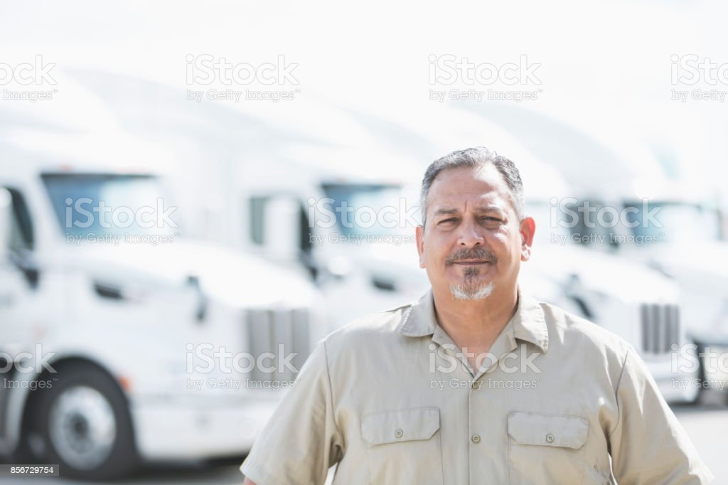 Hispanic man standing in front of semi-trucks stock photo