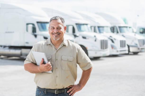 Hispanic man standing in front of semi-trucks - foto stock