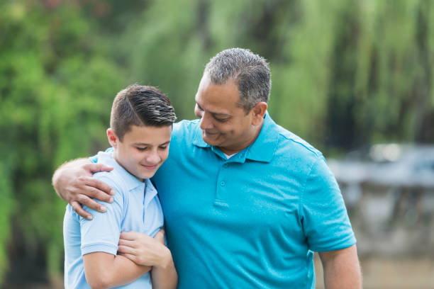 Hispanic man talking with teenage son An Hispanic man in his 40s standing in the park, talking with his 15 year old son, arm around his shoulder. The teenager is mixed race Caucasian and Hispanic. encouragement stock pictures, royalty-free photos & images
