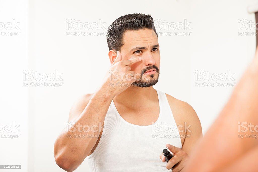 Hispanic man using an under eye cream stock photo