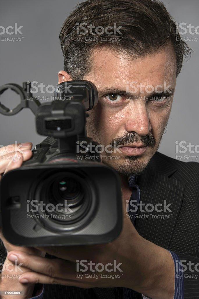 Hispanic man with beard holding a video camera royalty-free stock photo