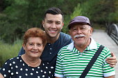 Hispanic man with his parents outdoors.
