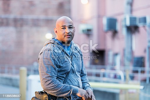 A mature Hispanic man in his 40s standing alone on a city street. He is wearing casual clothing, a hooded shirt. He has a serious expression on his face, sideways glance at the camera. He is a muscular man with a large build, a shaved head, and round face with stubble.