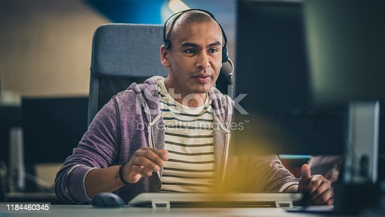 Hispanic man with a headset using a computer while talking to a customer.