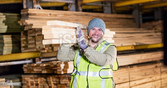 A mid adult Hispanic man in his 30s working at a warehouse at a lumberyard or home improvement store. He is carrying a stack of lumber on his shoulder, smiling at the camera.