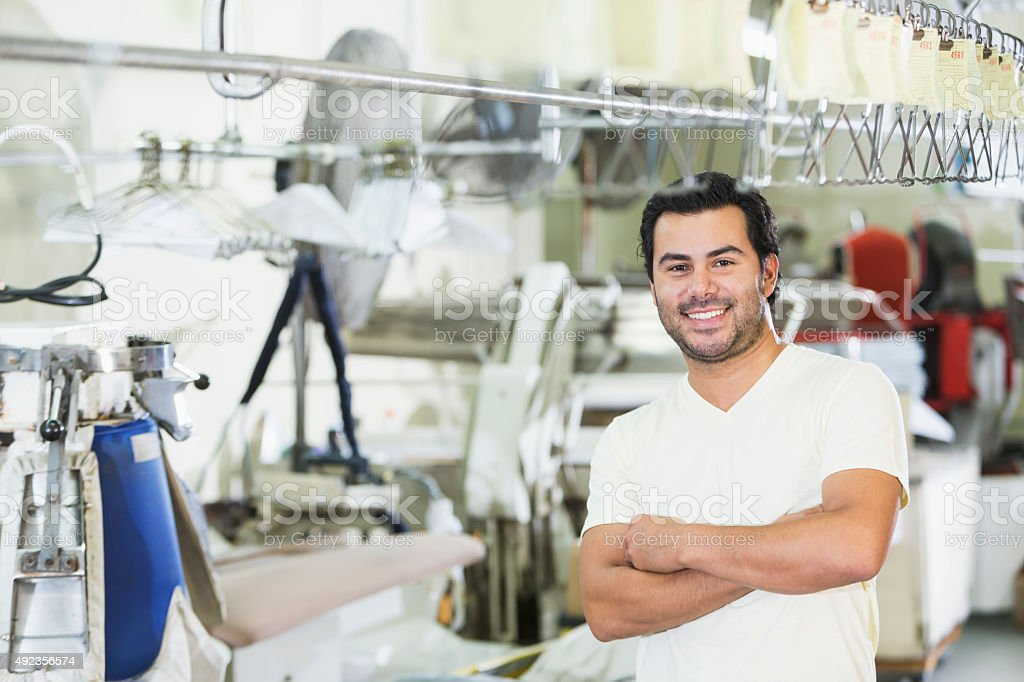 Hispanic man working in dry cleaners stock photo