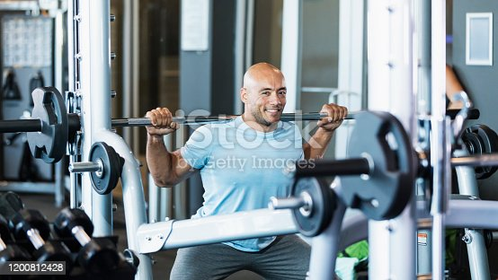 A mid adult Hispanic man in his 30s working out at the gym. He is an athlete with a muscular build, lifting a barbell on his shoulders. He is smiling at the camera.