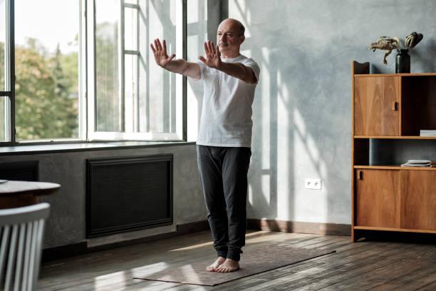 Hispanic man working out, yoga in basic standing asana tadasana stock photo