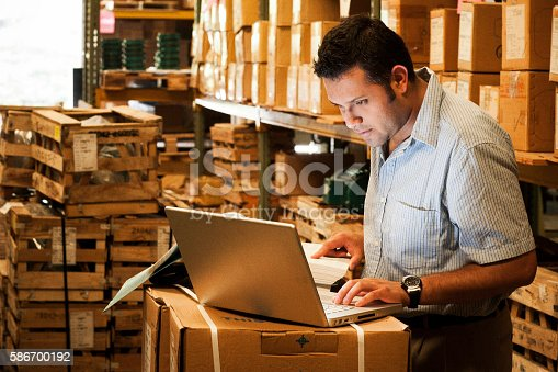 Hispanic manager working in warehouse going over inventory and shipping and receiving.