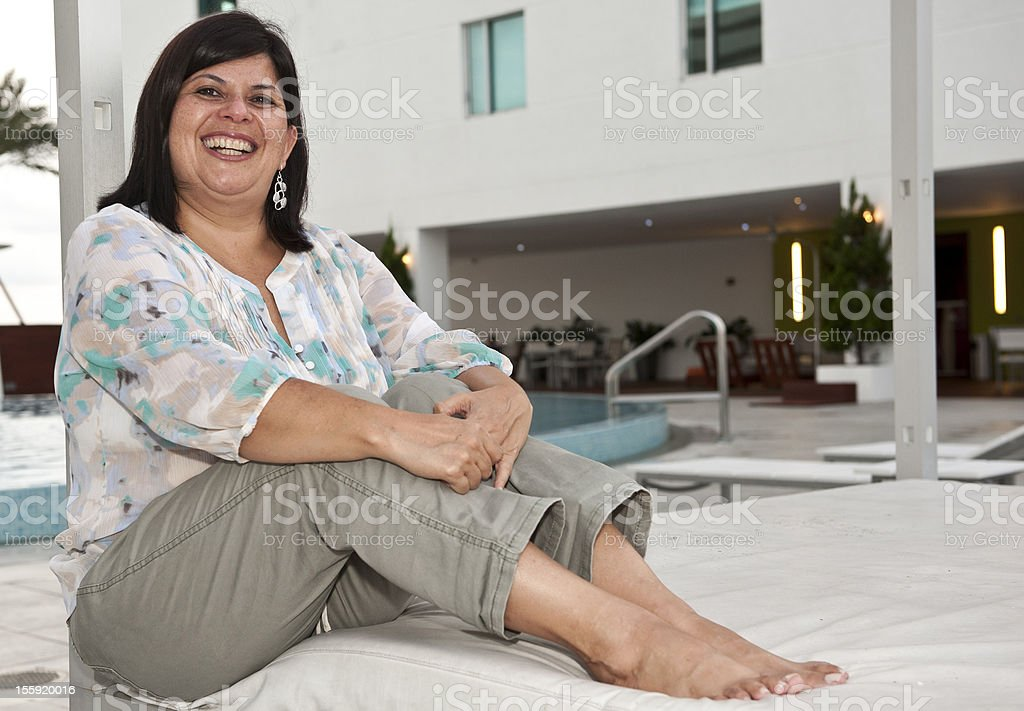 Hispanic mature woman posing near the swimming pool royalty-free stock photo
