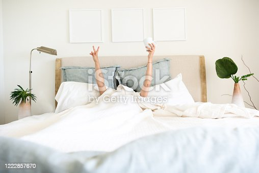 Hispanic mature woman waking up in bed with coffee mug in hand underneath the bed cover