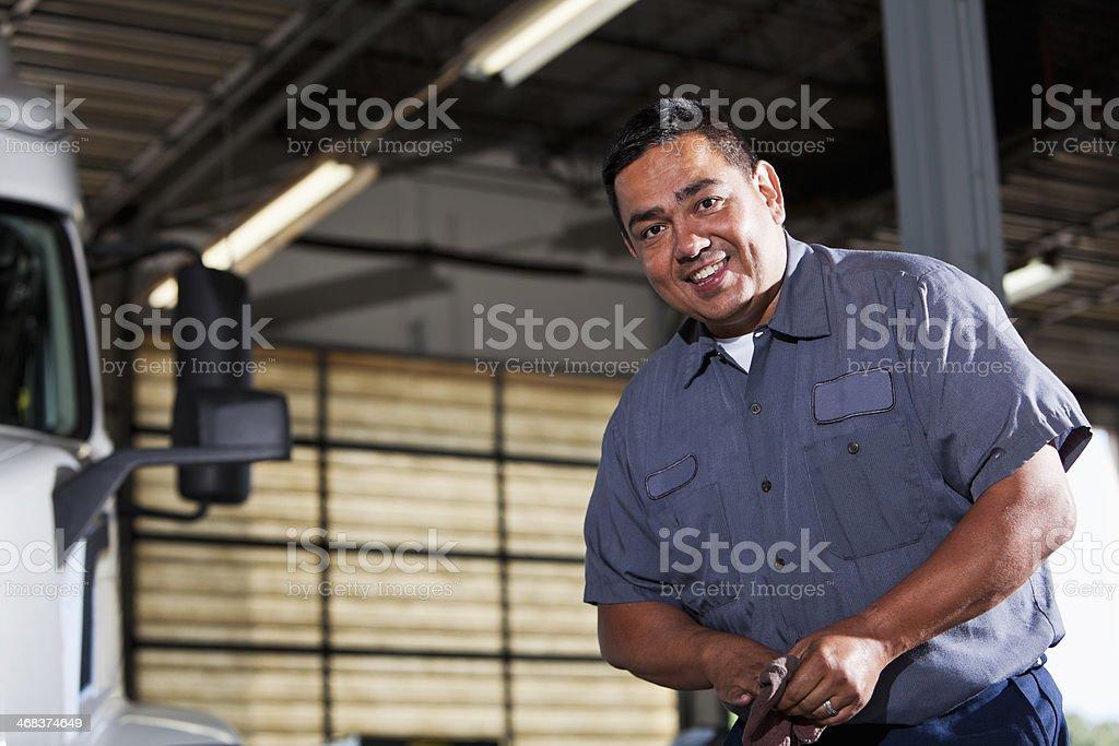 Hispanic mechanic in garage with truck royalty-free stock photo
