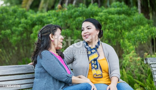 A young Hispanic woman in her 20s sitting on a park bench with her mother, a mature woman in her 50s. They are talking and smiling, enjoying hanging out together.