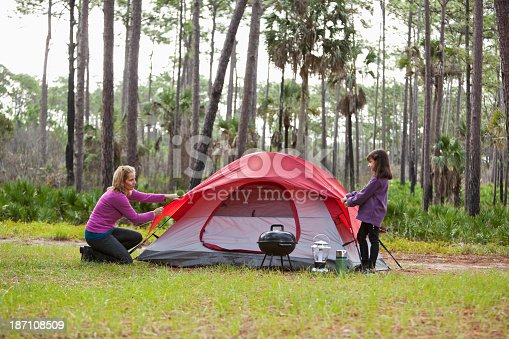 Hispanic mother (30s) and daughter (7 years) camping, pitching the tent.