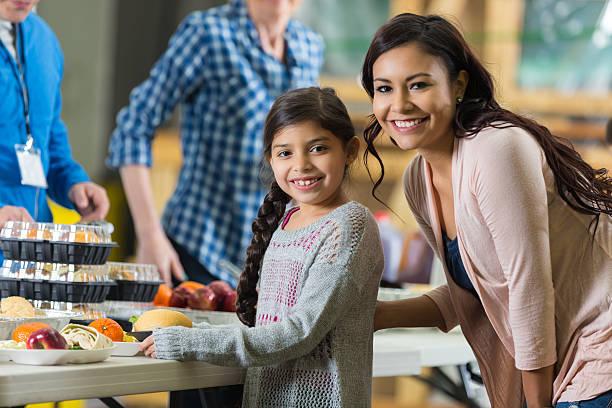 hispanische mutter und tochter essen mahlzeit im community food bank - küchenorganisation stock-fotos und bilder