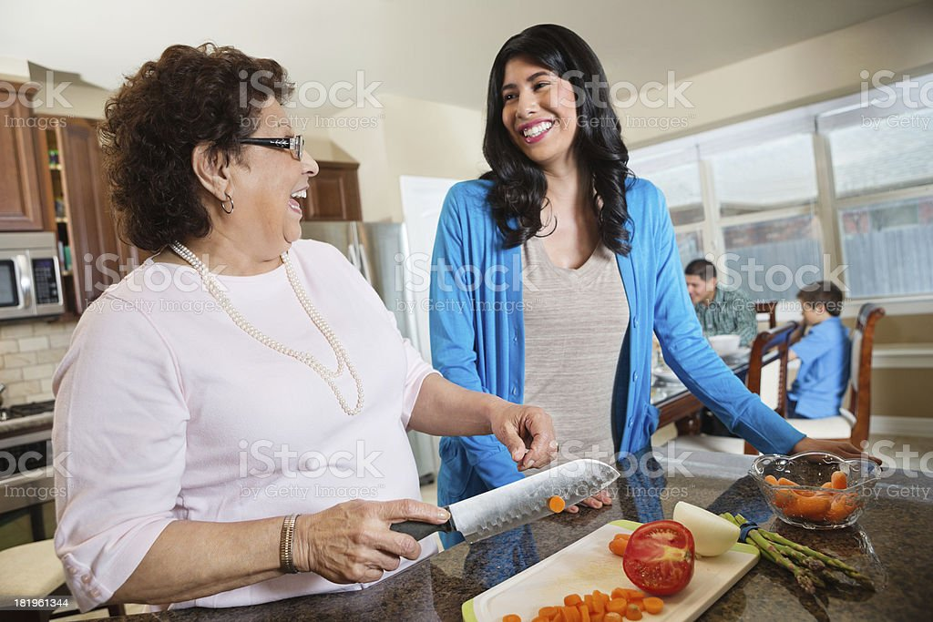 Hispanic mother and grandmother laughing while preparing meal together stock photo